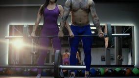 Atleta de sexo femenino muscular que hace entrenamiento del ABS Hombre fuerte que hace ejercicio del arrebatamiento del barbell e metrajes
