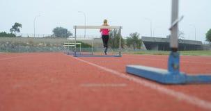 Atleta de sexo femenino que activa en una pista corriente 4k almacen de video