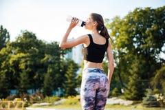 Atleta de sexo femenino que bebe de la botella de agua después de entrenamiento en el estadio Foto de archivo libre de regalías