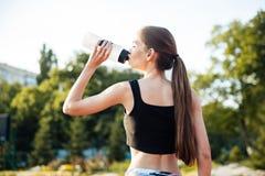 Atleta de sexo femenino que bebe de la botella de agua después de entrenamiento en el estadio Imágenes de archivo libres de regalías