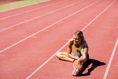Atleta de sexo femenino que calienta en la pista corriente Foto de archivo libre de regalías