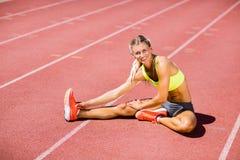 Atleta de sexo femenino que calienta en la pista corriente Imagenes de archivo