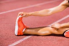 Atleta de sexo femenino que calienta en la pista corriente Fotografía de archivo libre de regalías