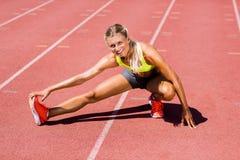 Atleta de sexo femenino que calienta en la pista corriente Fotos de archivo libres de regalías