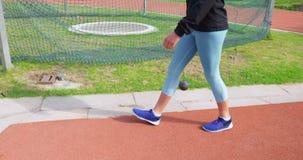 Atleta de sexo femenino que camina en el circuito de carreras 4k almacen de metraje de vídeo
