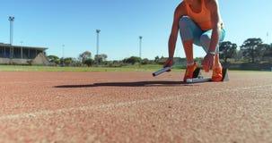 Atleta de sexo femenino que consigue listo para la raza en el circuito de carreras 4k almacen de video