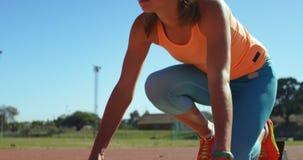 Atleta de sexo femenino que consigue listo para la raza en el circuito de carreras 4k almacen de metraje de vídeo