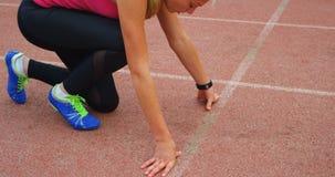 Atleta de sexo femenino que consigue listo para la raza en la pista de funcionamiento 4k almacen de video