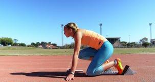 Atleta de sexo femenino que consigue listo para la raza en la pista de funcionamiento 4k almacen de metraje de vídeo
