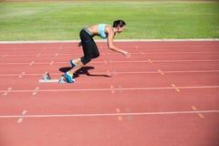 Atleta de sexo femenino que corre de bloques el comenzar Imagen de archivo libre de regalías