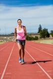 Atleta de sexo femenino que corre en la pista corriente Imágenes de archivo libres de regalías