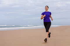 Atleta de sexo femenino que corre en la playa Imagenes de archivo