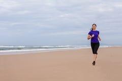 Atleta de sexo femenino que corre en la playa en un día del otoño Foto de archivo libre de regalías