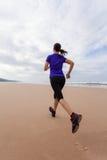 Atleta de sexo femenino que corre en la playa en un otoño Fotos de archivo