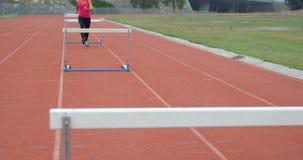 Atleta de sexo femenino que corre sobre obstáculos en una pista corriente 4k almacen de video
