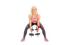 Atleta de sexo femenino que ejercita con dos pequeños barbells Foto de archivo libre de regalías