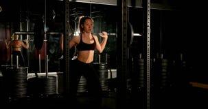 Atleta de sexo femenino que ejercita con el barbell 4k almacen de video