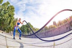 Atleta de sexo femenino que ejercita con la cuerda de la batalla al aire libre Imágenes de archivo libres de regalías