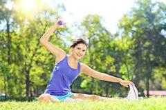 Atleta de sexo femenino que ejercita con pesa de gimnasia en un parque Imagen de archivo libre de regalías