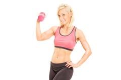 Atleta de sexo femenino que ejercita con una pesa de gimnasia rosada Imágenes de archivo libres de regalías