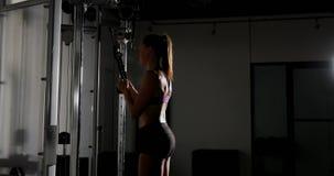 Atleta de sexo femenino que ejercita en la máquina 4k del tríceps almacen de video