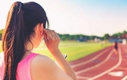 Atleta de sexo femenino que escucha la música en una pista corriente Fotos de archivo