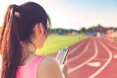 Atleta de sexo femenino que escucha la música en una pista corriente Foto de archivo libre de regalías