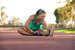 Atleta de sexo femenino que estira en una pista corriente Fotografía de archivo