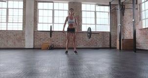 Atleta de sexo femenino que hace entrenamiento del levantamiento de pesas metrajes
