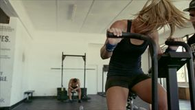 Atleta de sexo femenino que hace entrenamiento intenso en la bici del gimnasio con el coche metrajes