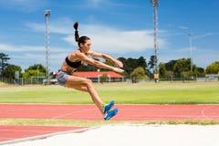 Atleta de sexo femenino que realiza un salto de longitud imágenes de archivo libres de regalías