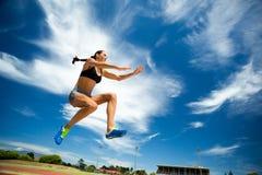 Atleta de sexo femenino que realiza un salto de longitud imagenes de archivo