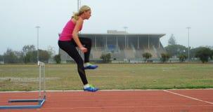 Atleta de sexo femenino que salta sobre obstáculos en una pista corriente 4k almacen de video