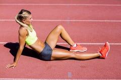 Atleta de sexo femenino que se sienta en la pista corriente Imagenes de archivo