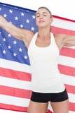 Atleta de sexo femenino que sostiene la bandera americana con los ojos cerrados Fotos de archivo libres de regalías