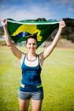 Atleta de sexo femenino que sostiene una bandera brasileña Imagen de archivo libre de regalías