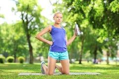 Atleta de sexo femenino que sostiene una botella de agua y que descansa en un parque Fotografía de archivo