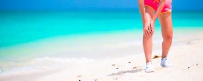 Atleta de sexo femenino que sufre de dolor en pierna mientras que ejercita en la playa blanca Imagen de archivo