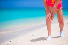 Atleta de sexo femenino que sufre de dolor en pierna mientras que ejercita en la playa blanca Imagenes de archivo