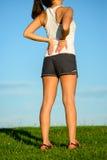 Atleta de sexo femenino que sufre dolor de espalda Imagen de archivo libre de regalías