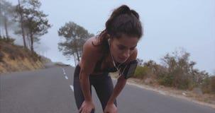 Atleta de sexo femenino que toma la respiración del funcionamiento almacen de metraje de vídeo