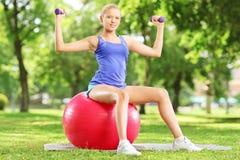 Atleta de sexo femenino rubio en el parque que se sienta en bola y que ejercita con Imagen de archivo libre de regalías