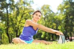 Atleta de sexo femenino sonriente que estira en un parque Fotos de archivo libres de regalías