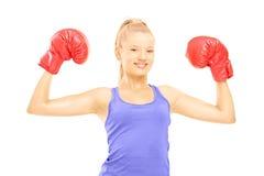 Atleta de sexo femenino sonriente que lleva guantes y la presentación de boxeo rojos Imagen de archivo libre de regalías