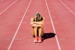 Atleta de sexo femenino trastornado que se sienta en pista corriente Imagen de archivo libre de regalías
