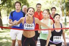 Atleta de sexo femenino Winning Marathon Race Imagenes de archivo