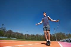 Atleta de sexo masculino activo que salta la cuerda afuera Fotografía de archivo libre de regalías