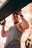 Atleta de sexo masculino atractivo joven que hace tirón-UPS paralelo en el parque imagen de archivo libre de regalías