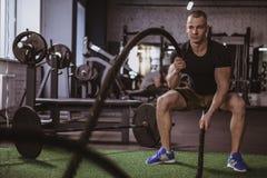 Atleta de sexo masculino del crossfit que se resuelve con las cuerdas de la batalla en el gimnasio fotografía de archivo libre de regalías