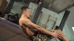 Atleta de sexo masculino descamisado joven Training Abdominal y músculos de la base metrajes
